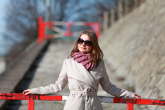 Beautiful young woman wearing a coat on a sunny winter day. Blonde girl with sunglasses leaning on a red barrier Royalty Free Stock Photo