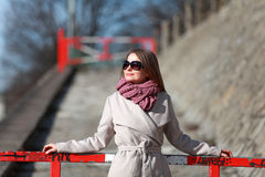 Beautiful young woman wearing a coat on a sunny winter day. Blonde girl with sunglasses leaning on a red barrier stock image