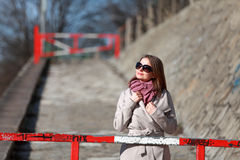 Beautiful young woman wearing a coat on a sunny winter day. Blonde girl with sunglasses leaning on a red barrier Stock Photo