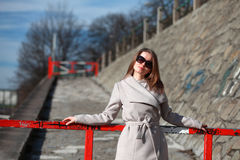 Beautiful young woman wearing a coat on a sunny winter day. Blonde girl with sunglasses leaning on a red barrier Stock Images