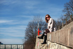 Beautiful young woman wearing a coat on a sunny winter day. Blonde girl with sunglasses sitting on the street stock photo