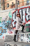 Beautiful young woman wearing a coat on a sunny winter day. Blonde girl with sunglasses standing on stairs with graffiti Stock Photo