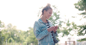Beautiful young woman wearing denim jacket typing on phone in a city park. Stock Photography