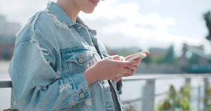 Beautiful young woman wearing denim jacket typing on phone in a city park during sunny day. stock video footage