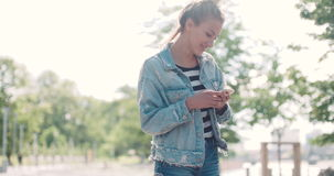 Beautiful young woman wearing denim jacket typing on phone in a city park during sunny day. stock footage