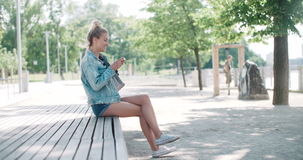 Beautiful young woman wearing denim jacket typing on phone in a city park during sunny day. stock video