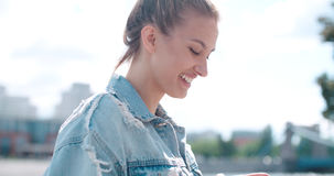 Beautiful young woman wearing denim jacket typing on phone in a city park during sunny day. Stock Photography