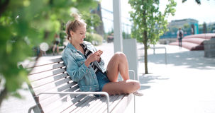 Beautiful young woman wearing denim jacket typing on phone in a city park during sunny day. Royalty Free Stock Photo