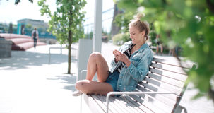 Beautiful young woman wearing denim jacket typing on phone in a city park during sunny day. Royalty Free Stock Images