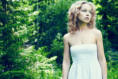Beautiful young woman wearing elegant white dress standing on a Royalty Free Stock Photography
