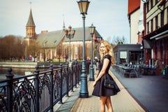 Beautiful girl walking in the street of city. Beautiful young woman wearing fashion black dress walking in the street of the city. Fishing village in Kaliningrad Stock Images