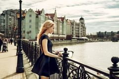 Beautiful young woman wearing fashion black dress walking in the. Street of Fishing village in Kaliningrad city. Focus on girl face Stock Images
