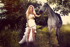 Beautiful young bride with horse in garden. Beautiful young woman wearing fashionable white dress posing with horse in garden on sunny day Stock Image