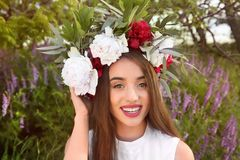 Beautiful young woman wearing floral wreath. On blurred background Stock Image