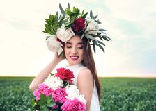 Beautiful young woman wearing floral wreath. In green field Stock Photos