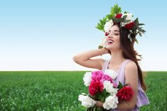 Beautiful young woman wearing floral wreath. In green field Stock Photo