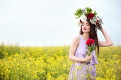 Beautiful young woman wearing floral wreath. In green field Royalty Free Stock Photos