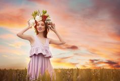 Beautiful young woman wearing floral wreath. In green field Stock Image