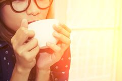 Beautiful young woman wearing glasses drinking coffee in the caf. E background Stock Photos