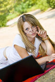 Beautiful young woman wearing glasses with laptop Stock Photography