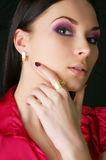 Beautiful young woman wearing golden jewelry Royalty Free Stock Photos