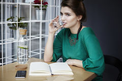 Beautiful young woman wearing green drinking pure water in cafe, having breakfast, opened book spread on table. Stock Photo