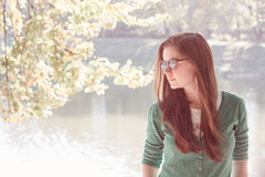 Beautiful young woman wearing green sweater and sun glasses Stock Image