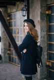 Beautiful young woman wearing hat and dark-blue coat walking on a city street Royalty Free Stock Images