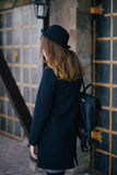 Beautiful young woman wearing hat and dark-blue coat walking on a city street Stock Photos