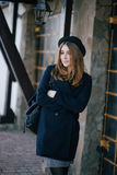 Beautiful young woman wearing hat and dark-blue coat walking on a city street Stock Image