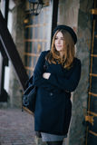 Beautiful young woman wearing hat and dark-blue coat walking on a city street Royalty Free Stock Photography