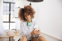 Beautiful young woman wearing headphones and listening musing on mobile phone. Beautiful young afro american woman using mobile phone at home royalty free stock photo