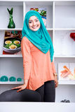 Beautiful young woman wearing hijab standing with shelf and some Royalty Free Stock Images