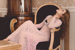 Beautiful young woman wearing lace sitting in Stock Photography
