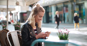 Beautiful young woman wearing leather jacket typing on phone during sunny day. Royalty Free Stock Photos