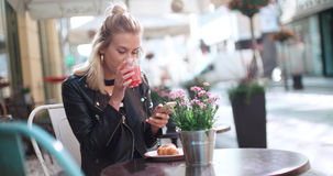 Beautiful young woman wearing leather jacket typing on phone during sunny day. Royalty Free Stock Photography