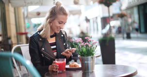 Beautiful young woman wearing leather jacket typing on phone during sunny day. Stock Photography