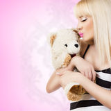 Beautiful young woman wearing pajamas embraces teddy bear Stock Photo