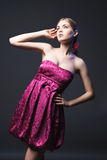 Beautiful young woman wearing pink dress. On a dark background Royalty Free Stock Photos