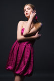 Beautiful young woman wearing pink dress. On a dark background Stock Images