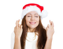 Beautiful young woman wearing red santa claus hat crossing fingers, closing eyes, wishing praying for a miracle Stock Image
