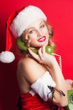 Beautiful young woman wearing Santa Claus costume. Holding green old phone receiver against red background Stock Image