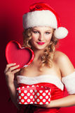 Beautiful young woman wearing Santa Claus costume. Holding heart-shaped gift box against red background Stock Photos