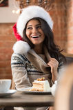 Beautiful young woman wearing Santa Claus red hat sitting at caf Stock Photography