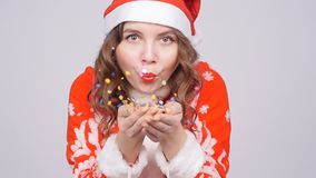 Young woman wearing Santa`s hat blowing away confetti. Beautiful young woman wearing Santa`s hat blowing away confetti stock video