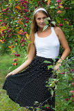 Beautiful young woman wearing spotted skirt standing at the apple tree Royalty Free Stock Photos