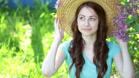 Beautiful young woman wearing straw hat and sitting in the park stock footage