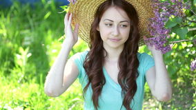 Beautiful young woman wearing straw hat and sitting in the park stock video footage