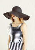 Beautiful young woman wearing a striped dress, black straw hat Stock Photo