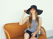 Beautiful young woman wearing a striped dress, black straw hat and handbag clutch Royalty Free Stock Images